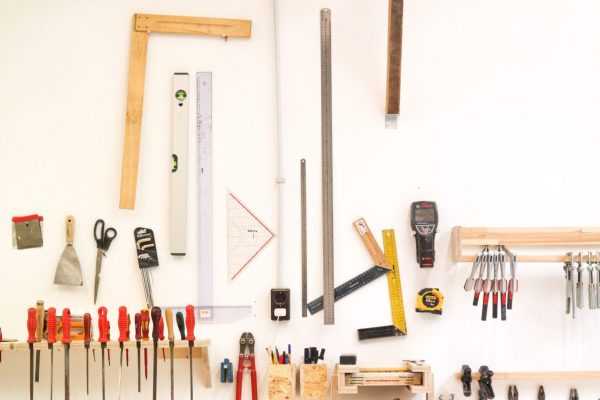 assorted hand tools on white table
